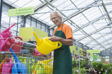 looking for job: Male gardener arranging colourful watering cans, Augsburg, Bavaria, Germany LANG_EVOIMAGES