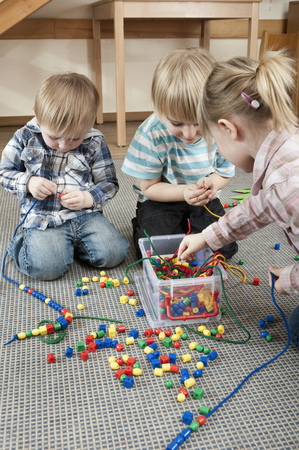 sitting on the ground: Three kids playing with coloured wooden perls