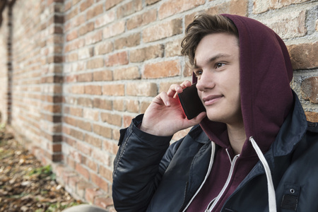 Young man talking on mobile phone and leaning against brick wall, Munich, Bavaria, Germany LANG_EVOIMAGES