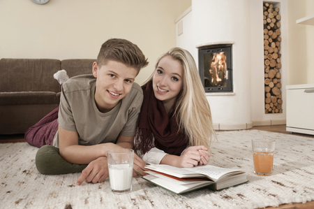 Teenage couple with book lying on carpet in front of fireside LANG_EVOIMAGES