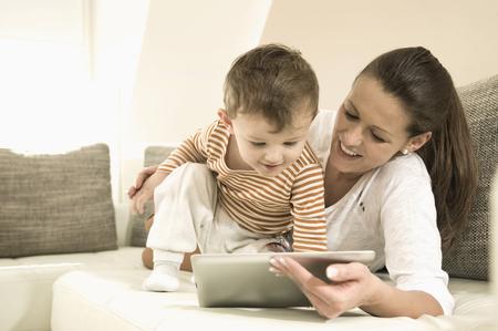 Madre e hijo usando la tableta digital en la sala de estar, sonriendo