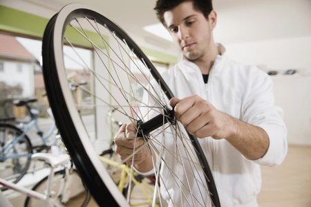 Young man working on bicycle tire