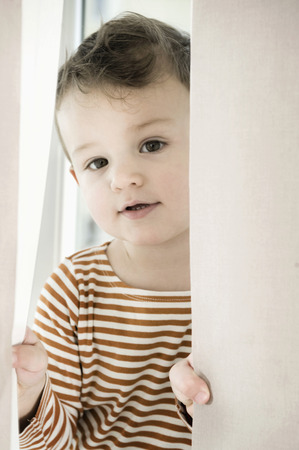 twee: Portrait of boy playing with curtain LANG_EVOIMAGES
