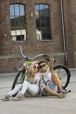 v cycle: Teenage couple sitting on street with bicycle and showing peace sign, smiling