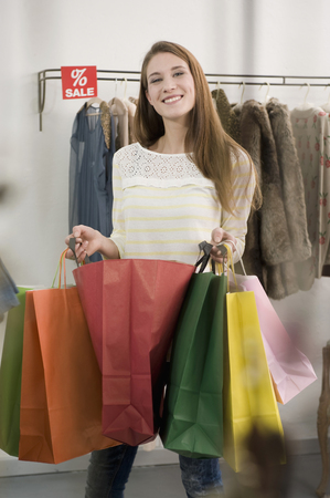 coathangers: Portrait of young woman holding shopping bags, smiling