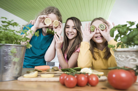 actinidia deliciosa: Girls in kitchen making faces with fruit LANG_EVOIMAGES