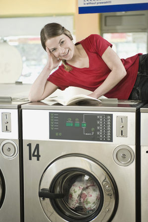 beings: Portrait of young woman reading book on top of machine, smiling