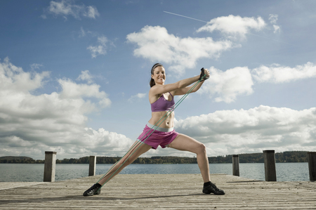 Woman woman exercising with resistance band, Woerthsee, Bavaria, Germany LANG_EVOIMAGES