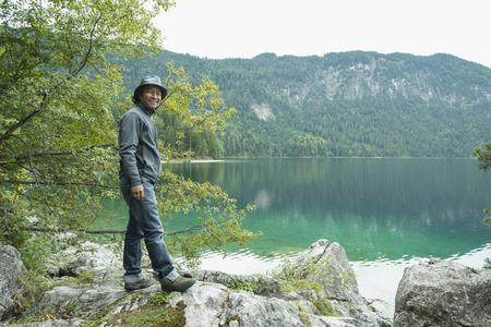 german ethnicity: Tourist standing on rock at Eibsee lake, Bavaria, Germany