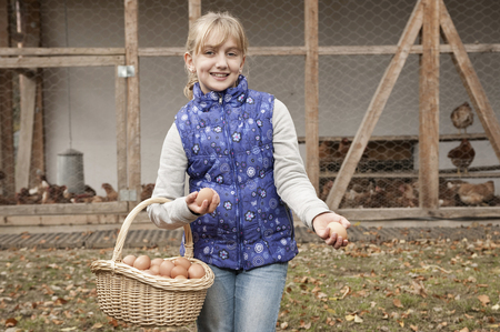 non stock: Blond girl holding basket with eggs on farm
