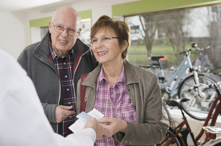 65 70 years: Senior Couple paying from credit card for bicycle LANG_EVOIMAGES