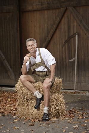 Hombre en lederhosen en la granja, Barvaria, Alemania LANG_EVOIMAGES