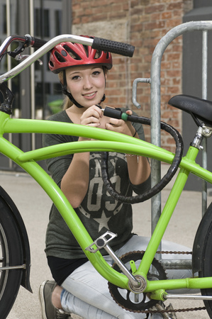 Portrait of teenage girl locking bicycle, smiling
