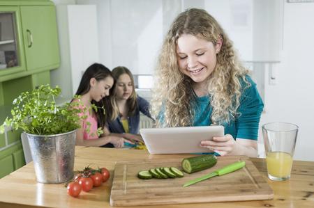 10 11 years: Girls in kitchen with digital tablet, preparing vegetables LANG_EVOIMAGES