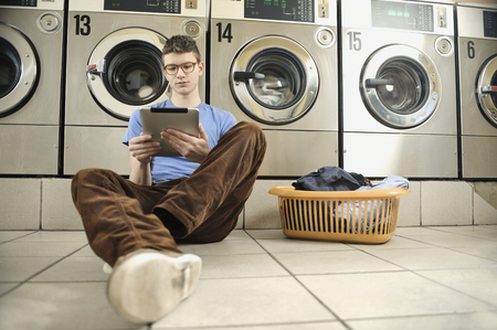 launderette: Young man using digital tablet in laundry