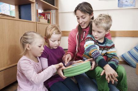 sitting on the ground: Female educator and three kids in kindergarten