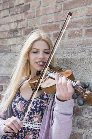 violinista: Caucasian teenage girl playing violin in front of brick wall, Munich, Bavaria, Germany LANG_EVOIMAGES