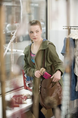 coathangers: Young woman stealing something in fashion store LANG_EVOIMAGES
