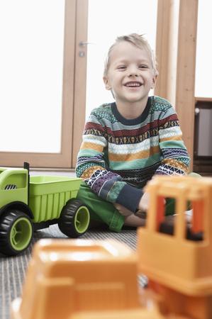 sitting on the ground: Portrait of smiling little boy sitting on ground of his kindergarten