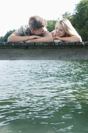 2 way: Teenage couple lying side by side on a jetty at lake LANG_EVOIMAGES