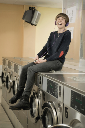 launderette: Young woman listening music on top of washing machine, smiling LANG_EVOIMAGES