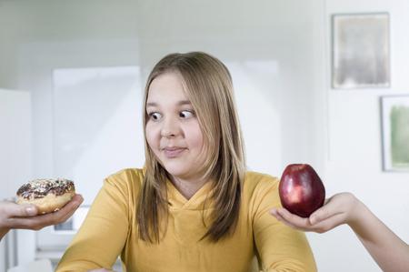 10 11 years: Girl choosing between apple and doughnut