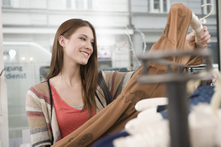coathangers: Young woman shopping in fashion store, smiling