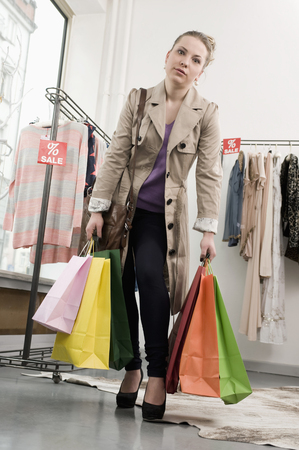 Portrait of young woman holding shopping bags