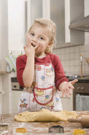 Girl nibbling dough, portrait LANG_EVOIMAGES