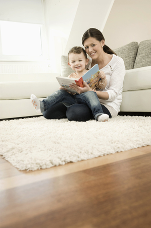twee: Mother and son are watching storybook, smiling