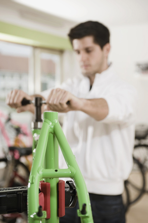 Young man working on bicycle frame LANG_EVOIMAGES