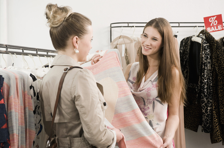 customer facing: Sales girl with customer in fashion store