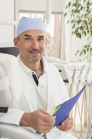 Portrait of dentist holding file and smiling, Munich, Bavaria, Germany