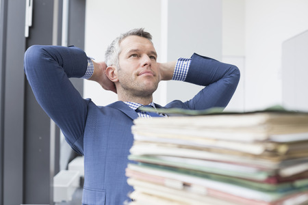 businessman pondering documents: Businessman relaxing in office, Leipzig, Saxony, Germany