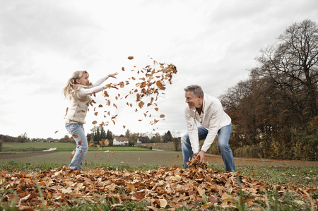 ardor: Happy girl with father throwing autumn leaves