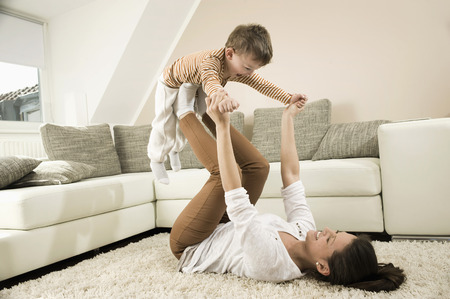 romp: Mother and son are romping in living room, smiling LANG_EVOIMAGES