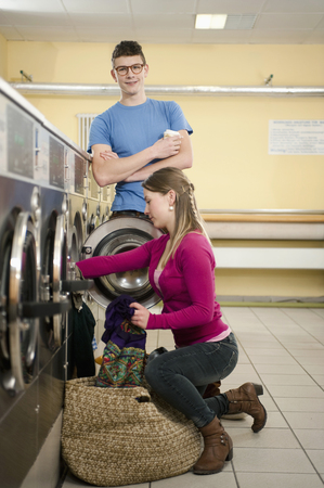 cowering: Young couple filling up cloths in washing machine