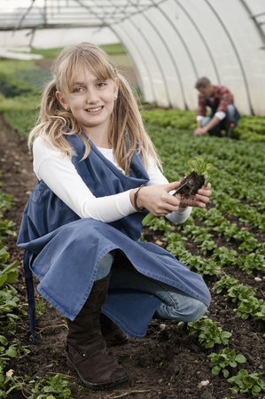 cowering: Smiling blond girl in greenhouse