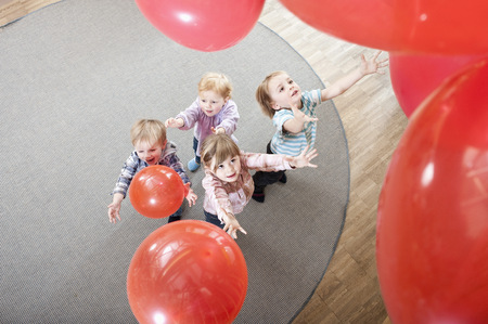 Four kids playing with red balloons in kindergarten, elevated view LANG_EVOIMAGES