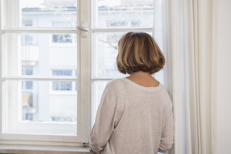 radiator: Rear view of senior woman looking through a window, Munich, Bavaria, Germany LANG_EVOIMAGES