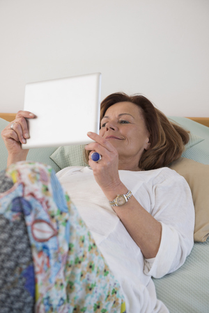 Senior woman lying on bed and using a digital tablet, Munich, Bavaria, Germany