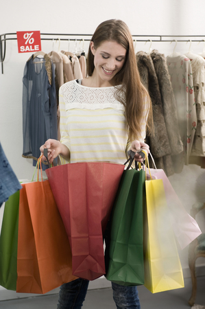 coathangers: Young woman holding shopping bags, smiling LANG_EVOIMAGES