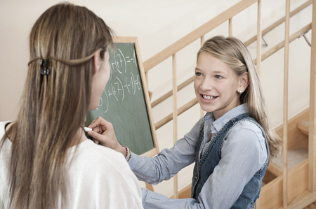 Female childcare assistant helping schoolgirl by doing homework