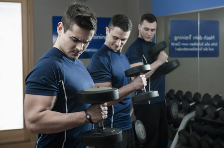 conformance: Three young men doing weight training in gym LANG_EVOIMAGES