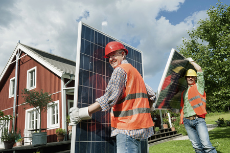 Two workmen installing solar panel house LANG_EVOIMAGES