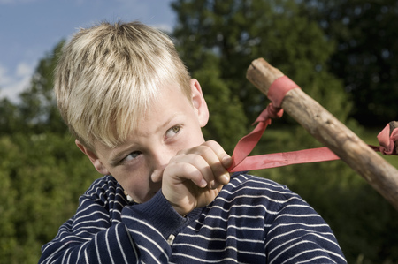 trouble free: Portrait boy holding handmade wooden slingshot