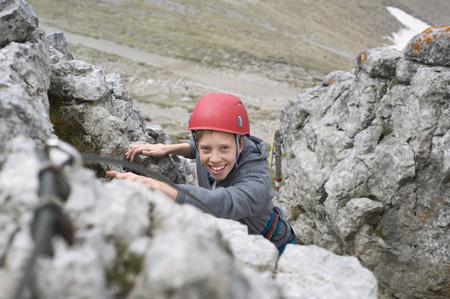 self conceit: Boy helmet mountains climbing Alps cliff LANG_EVOIMAGES