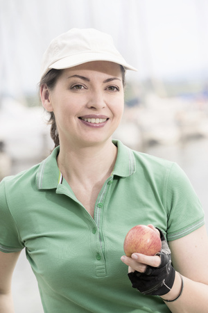 le cap: Mature woman eating an apple at lakeside and smiling, Bavaria, Germany