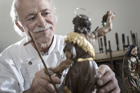 antiquity: Senior sculptor works on a Jesus Christ statue at workshop, Bavaria, Germany LANG_EVOIMAGES