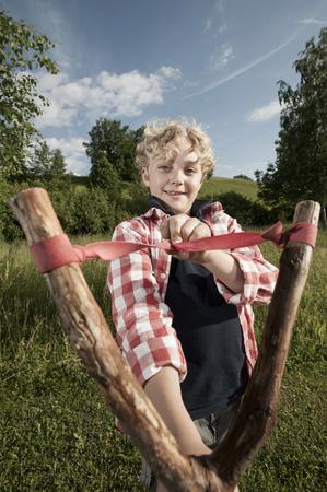 lust for life: Young boy blond holding wooden slingshot